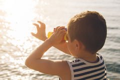 Little boy looks into the distance through binoculars Royalty Free Stock Images