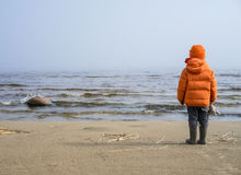 Little boy looks into the distance on lake Royalty Free Stock Images