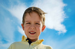 Little boy looks down on blue sky background horizontal Stock Photos