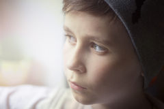 A little boy looks out the window and is sad. Light from the window Royalty Free Stock Photos