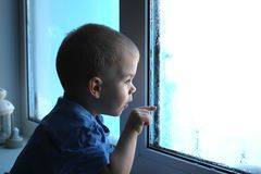 Little boy looks out the window shows a finger in the glass stock photography