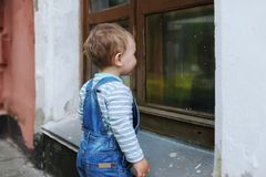 The little boy looks at the reflection in a window of the city building Stock Photography