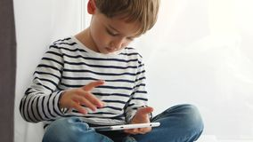 A little boy looks at the screen of the tablet, sitting by the window. The child runs his fingers up and down the touch stock video footage