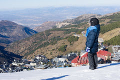 The little boy looks at the snow-covered town of Sierra Nevada. Royalty Free Stock Photography