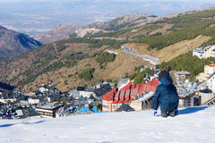 The little boy looks at the snow-covered town of Sierra Nevada. Royalty Free Stock Photos