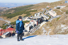 The little boy looks at the snow-covered town of Sierra Nevada. Stock Images