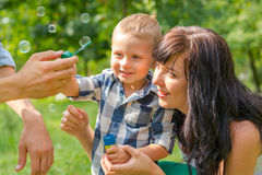A little boy looks on a soap bubbles. Dad holds his son`s hand a Royalty Free Stock Photography