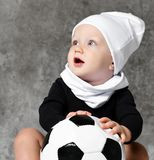 Cute image of baby holding a soccer ball. stock photos
