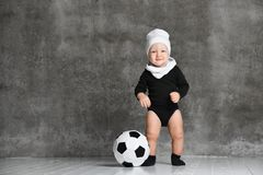 Little boy looks surprised aside, near a black and white football in his legs. wearing a white cotton hat and a black bodysuit royalty free stock photo