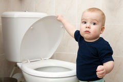 Little boy looks in the toilet Stock Photos