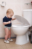 Little boy looks in the toilet Royalty Free Stock Photography