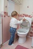Little boy looks in toilet Royalty Free Stock Image