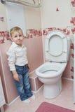 Little boy looks in toilet Stock Photos