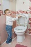 Little boy looks in toilet Royalty Free Stock Photo