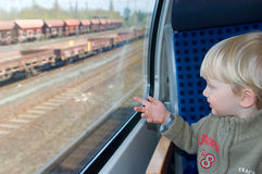 Little boy looks in train`s window Stock Images