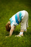 The little boy looks upside down. On grass Stock Photo