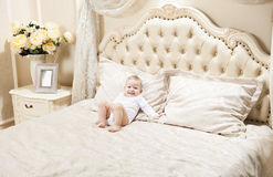Little boy lying on bed at home Stock Images