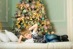 Little boy lying on the bed next to the spruce. New year Royalty Free Stock Photos