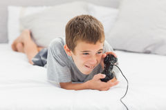 Little boy lying on bed playing video games Stock Images