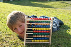 Little boy lying behind an abacus. Little boy lying behind the colorful abacus royalty free stock images