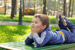 Little boy lying on the bench Stock Images