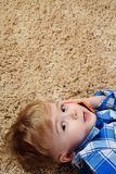A little boy is lying on the carpet and playing in the phone. Little boy using smartphone stock photography