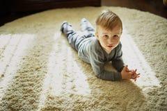 Little boy lying on the carpet stock photo