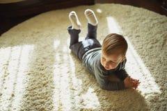 Little boy lying on the carpet royalty free stock photos