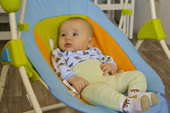 Little boy lying in the cradle and watch. Ing their parents stock images
