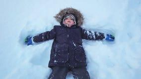 Boy lying in a deep snow royalty free stock photos