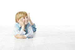 Little boy lying down on floor, looking at side Stock Photography