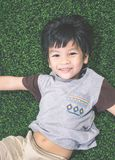 Little boy lying down on soccer field top view stock images