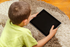 Little boy. Lying in the floor and looking at tablet Stock Photos