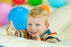 Little boy lying on the floor surrounded by colourful balloons Royalty Free Stock Photos