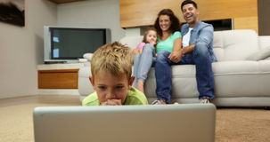 Little boy lying on floor using laptop with family behind him on sofa. At home in the living room stock video footage