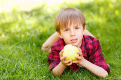 Little boy lying on grass with apple. Bitten off. Little boy lying on emerald-green grass with apple in his hands royalty free stock photo