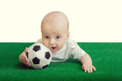 The Little boy lying on the grass with the ball Royalty Free Stock Photos