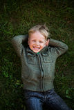 Little boy lying on grass and laughing. Portrait of a laughing little boy lying on green grass Stock Images