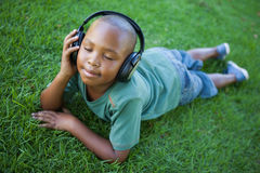 Little boy lying on grass listening to music with eyes closed Royalty Free Stock Photography