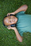 Little boy lying on grass listening to music with eyes closed Stock Photography