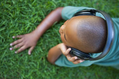 Little boy lying on grass listening to music Stock Images