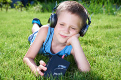 Little boy lying on grass with old audio cassette player Stock Image