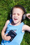 Little boy lying on grass with old audio cassette player Royalty Free Stock Photo