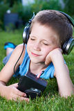 Little boy lying on grass with old audio cassette player Royalty Free Stock Photography