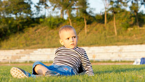 Little boy lying on green grass Stock Photography