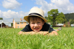 Little boy lying on a green grass Royalty Free Stock Photos