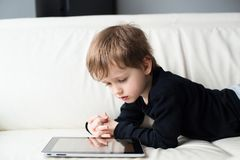 Little boy lying on his stomach and watch a movie on  tablet Stock Photography