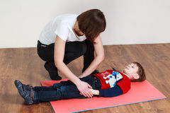 Little boy is lying on the mat at a gym, trainer is helping him stock image