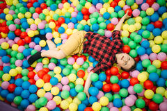 Little boy lying in a pile of colorful balloons Stock Images