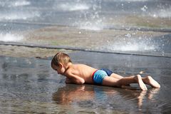 Little boy lying in puddle Royalty Free Stock Photography